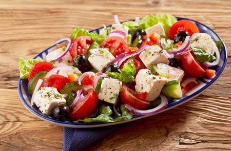 Plato de ensalada griega fresca y saludable con queso feta, aceitunas, pepino, lechuga, cebolla y tomate sazonados con hierbas en una mesa de madera