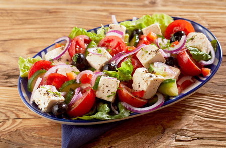 Dish of healthy fresh Greek salad with feta cheese, olives, cucumber, lettuce, onion and tomato seasoned with herbs on a wooden table