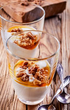 Delicious dessert with thick creamy natural Greek yogurt, honey and fresh walnuts served in two individual glasses