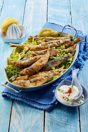 Healthy Greek cuisine with fried battered sardines dressed with lemon served in an old vintage dish with raita sauce to the side