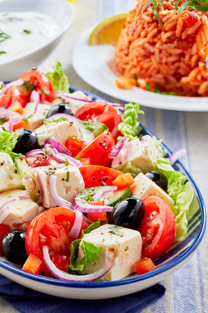 Close up on a plate of fresh Greek salad with feta cheese and olives seasoned with herbs served on a table with other side dishes Banco de Imagens