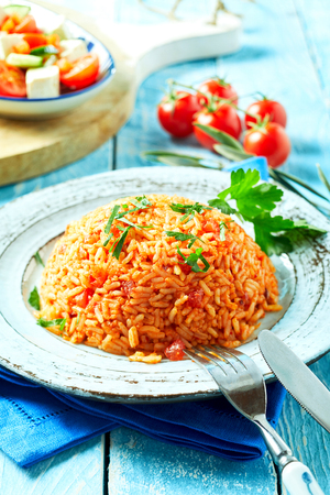 Serving of Greek tomato pilaf with long grained rice seasoned with fresh coriander on a rustic blue wood table with knife and fork