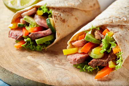 Two tortilla wraps with barbecued entrecote beef steak, avocado pear, chili peppers and lettuce in a close up view on a wooden board