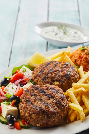 Spicy grilled Greek bifteki meat balls served with a fresh salad with feta cheese and olives, French fries and tomato rice Stockfoto