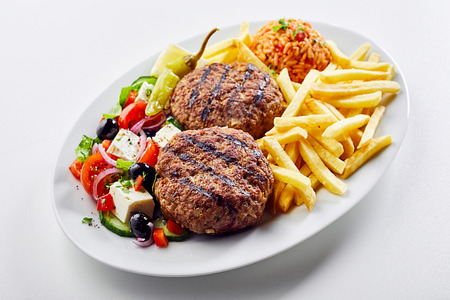 Spicy Greek bifteki meat balls served with a fresh salad, potato chips and tomato rice pilaf or domatorizo on an oval platter over white