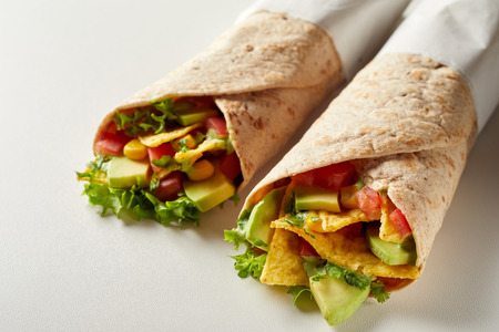 Avocado pear and nachos in a tortilla wrap with chili peppers and fresh salad ingredients close up on white