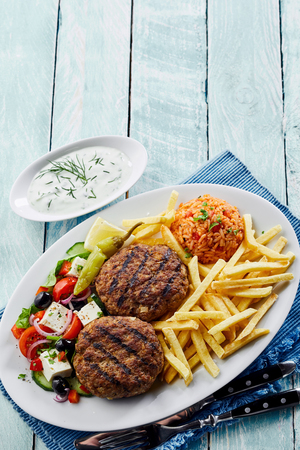 Traditional Greek cuisine with bifteki, or spicy meat balls, tomato rice pilaf, French fries and salad with feta and olives viewed from above with copy space Stock Photo