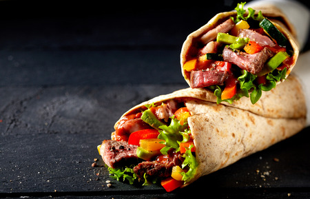 Tortilla wraps with tender sliced roasted entrecote beef steak, red chili pepper and salad trimmings on a dark slate background with copy space