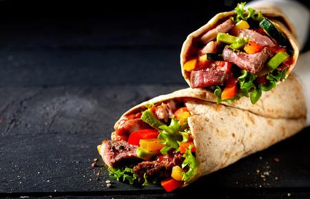 Tortillaverpackungen mit zartem geschnittenem gebratenem Entrecote-Rindfleischsteak, Pfeffer des roten Paprikas und Salatzutaten auf einem dunklen Schieferhintergrund mit Kopienraum Standard-Bild