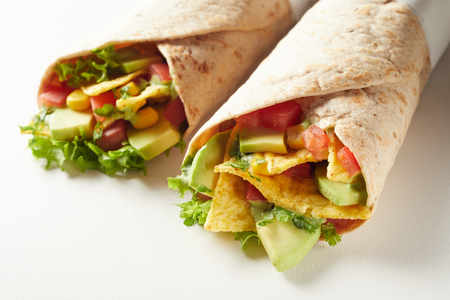 Mexican tortilla wraps with nachos, chili peppers, avocado and salad in a close up view for menu advertising on white