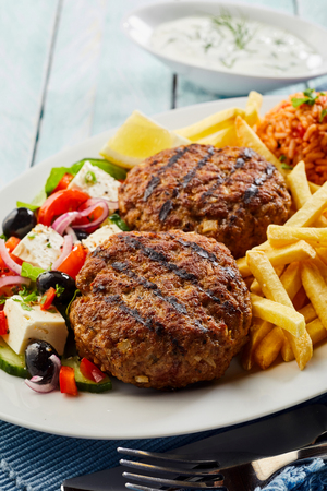 Spicy bifteki, frikadelle or frikkadel meatballs with minced beef and lamb served with Greek salad and French fries Stok Fotoğraf