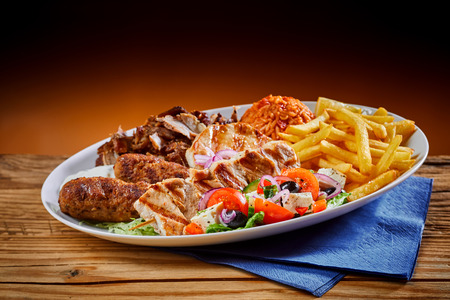 Plate full of Greek cuisine souvlaki with french fries and salad on wooden background