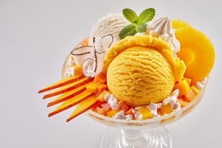 Gourmet dessert with artisanal mango and vanilla Italian ice cream garnished with sliced fresh fruit, white chocolate twirls and pineapple rings with whipped cream 写真素材