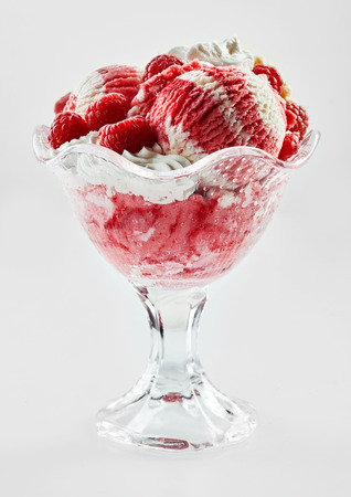 Raspberry and vanilla ice cream sundae with fresh fruit and whipped cream served in a glass bowl in a side view isolated on white