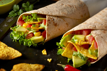 Two tortilla wraps with avocado pear, salad trimmings, chili peppers and nachos in a close up view ready to be served