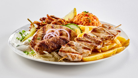 Traditional Greek mixed grill platter with grilled pork skewers, slouvaki ans souzuki steak served with potato chips, tomato rice pilaf and raiti