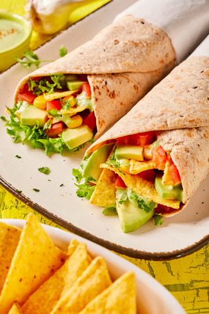 Speciality Mexican tortilla wraps with nachos, fresh avocado pear, chilli peppers and lettuce served on a rectangular platter