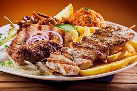 Greek grill platter with souvlaki, souzuki steak and grilled pork skewers served with refreshing raiti yogurt dressing and pilaf