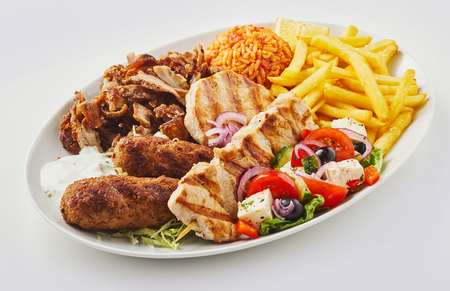 Greek mixed grill platter with salad, domatorizo and French Fries and a selection of souvlaki, souzuki steak and grilled pork skewers