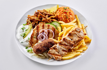 Regional Greek mixed grill with fried potato chips and tomato pilaf with souvlaki, souzuki steak and pork skewers served with raita Stock Photo