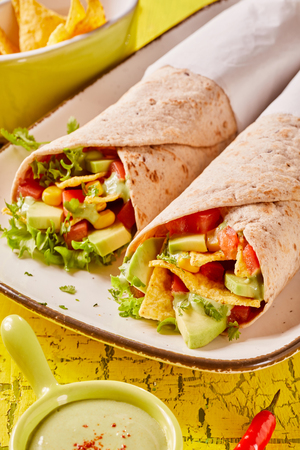 Tortilla wrap with nachos, avocado, fresh salad trimmings and guacamole on a bright yellow wooden background