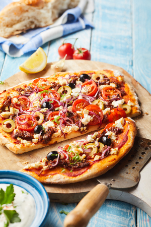 Tasty Greek pizza with olives, feta cheese, tomato and onion on a crispy thin base served sliced with raita to the side on a wooden chopping board Stock Photo