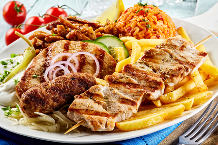 Greek grill plate with assorted meats, crispy potato chips, tomato rice pilaf and raiti in a close up view suitable for a menu Фото со стока