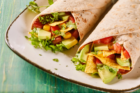 Speciality vegetarian tortilla wraps with nachos and avocado pear, chili peppers, lettuce and corn on a plate in a close up view suitable for a menu