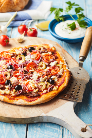 Whole Greek pizza with a thin crusty base topped with tomato, olives and feta cheese on an old wooden chopping board with spatula