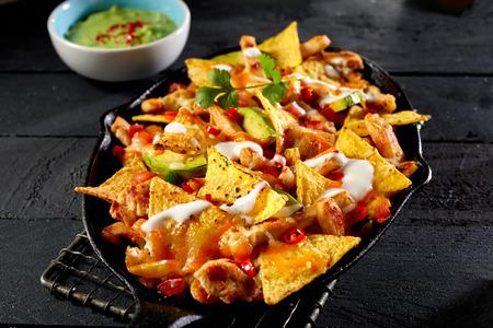 Chicken nacho tortilla with cream sauce served next to guacamole dip