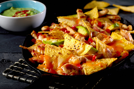 Tortilla nachos with meat, vegetables and guacamole dip