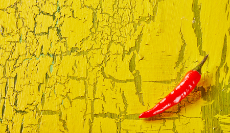 Colorful wooden cracked paint yellow background texture with a bright red fresh chili pepper in the lower corner and copy space