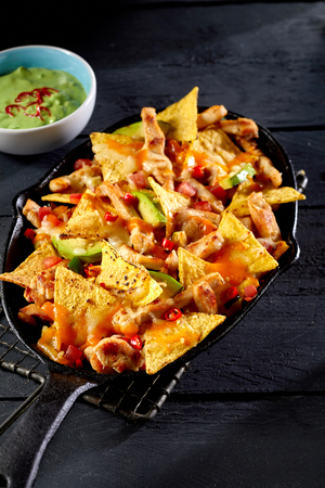 Nachos among meat, vegetables served with guacamole dip