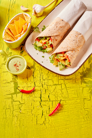 Two Mexican tortilla wraps with nachos, avocado, chili pepper and salad trimmings served with guacamole viewed from above on bright yellow cracked painted wood