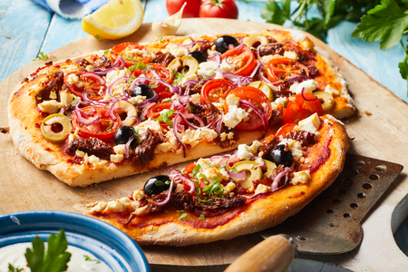 Tasty Greek pizza on a thin pastry base sliced and served with a spatula on a wooden board with a bowl of raita yogurt dressing to the side