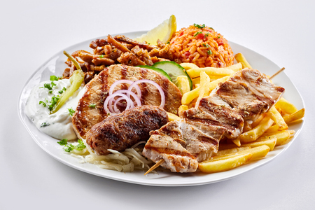 Mixed grill Greek platter with souvlaki, souzuki steak and spicy pork skewers served with tomato rice pilaf, potato chips and salad