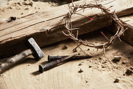 Sfondo di Pasqua raffigurante la crocifissione con una croce di legno rustica, martello, chiodi e corona di spine in una vista ravvicinata ritagliata sulla sabbia Archivio Fotografico