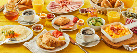 Easter breakfast panorama banner with a wholesome spread of assorted bread rolls, croissant, cheese, cold meats, orange juice, coffee, honey and preserves Stock Photo