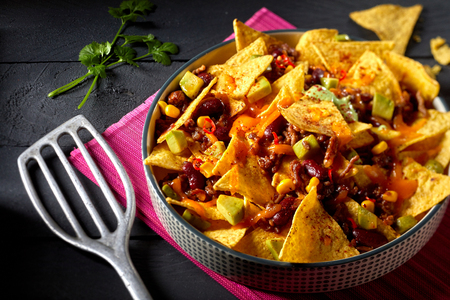 Spicy Tex-Mex chili con carne with nachos au gratin garnished with fresh coriander in a high angle view with spatula on a dark background Stock Photo