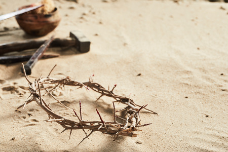 Crown of Thorns religious Easter background on sand with copy space and nails, hammer, spear and sponge in the background