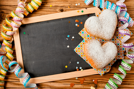 Two heart shaped cakes on a blank slate with copy space surrounded by colorful party streamers and confetti viewed from above