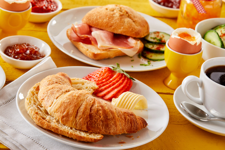 Freshly baked croissant with butter and strawberry served with a bacon roll, boiled egg, coffee and jellies or jams for a delicious spring breakfast Stok Fotoğraf - 96337530