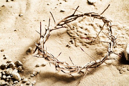 Natural plaited crown of thorns on sand with stones to the side in a concept of the Crucifixion of Christ and Easter Banco de Imagens
