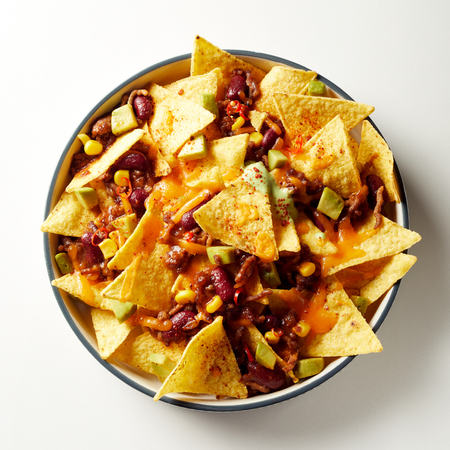 Mexican chili con carne with nachos topped with cheese and baked in an oven viewed from overhead in a dish over white