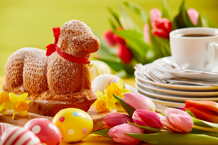 Delicious novelty lamb shaped Easter cake with a red ribbon collar on a spring table set with tulips, Easter eggs, plates and coffee