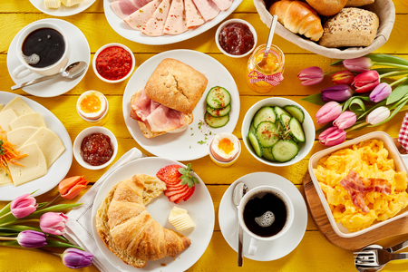 Healthy spring breakfast for two with an overhead view of a table spread with a croissant, bacon roll, bread buns, cold meats, cheese, assorted jams and coffee with two bouquets of fresh tulips