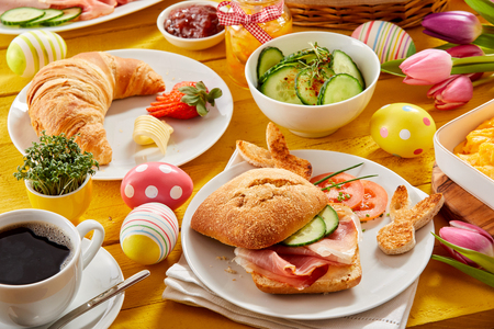 Tasty Easter brunch or spring breakfast with a fresh croissant, ham or bacon roll and coffee on a table decorated with colorful Easter eggs and tulips