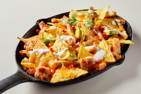 Pan full of chicken nacho tortilla with sauce Stock Photo