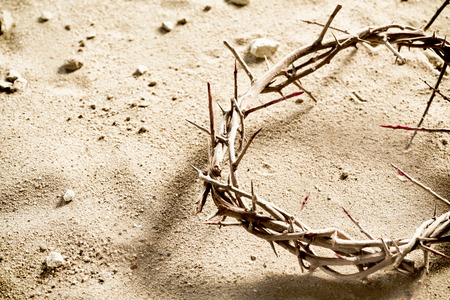 Circlet or Crown of Thorns on barren sand with copy space in a spiritual concept of the crucifixion and Easter