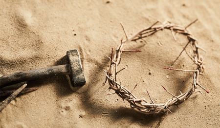 Religious Easter background with a natural twisted crown of thorns together with a hammer and old iron nail lying on sand